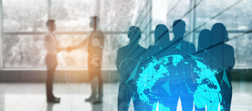 Silhouette of business partners shaking hands in office