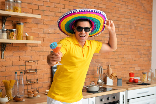 Handsome young man in sombrero hat and with cocktail at home