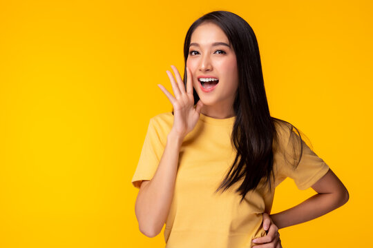 Surprised happy beauty asian woman look at camera in excitement Expressive facial expressions Presenting some product Beautiful girl act like a telling something Isolated on yellow background