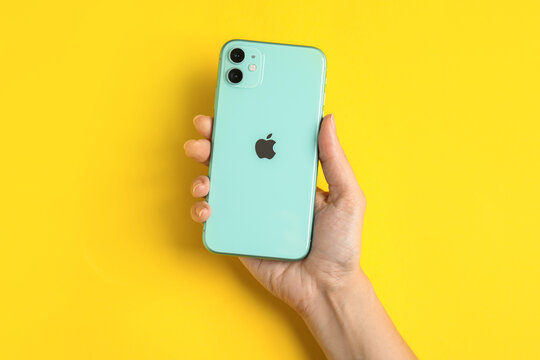 MYKOLAIV, UKRAINE - JULY 10, 2020: Woman holding new modern Iphone 11 Green on yellow background, top view