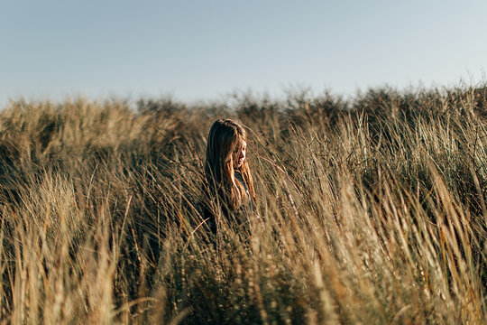 portrait of a girl in a meadow at sunset. Relaxing and enjoying nature and silence concept