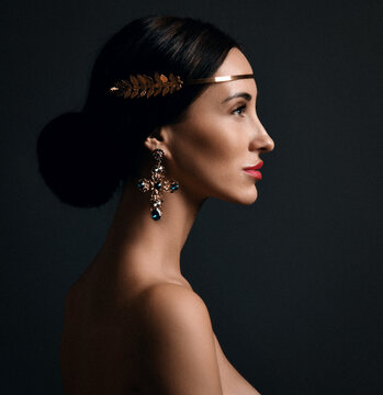 Profile of young smiling pretty woman model with elegant hairstyle, golden accessory on hair and massive earrings over dark background. Stylish female look, accessories concept