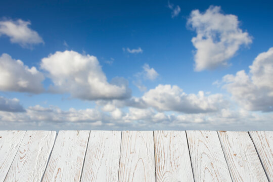 Empty white wooden table in front of a blurred background of some clouds ( cumulus ) . selective focus . space for copy and text. can be used to display or assemble your products.