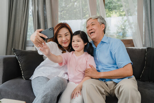 Asian grandparents selfie with granddaughter at home. Senior Chinese, grandpa and grandma happy spend family time relax using mobile phone with young girl kid lying on sofa in living room concept.