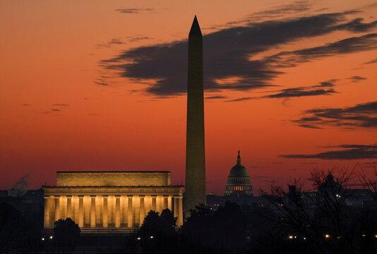 The sun rises behind landmarks of Washington