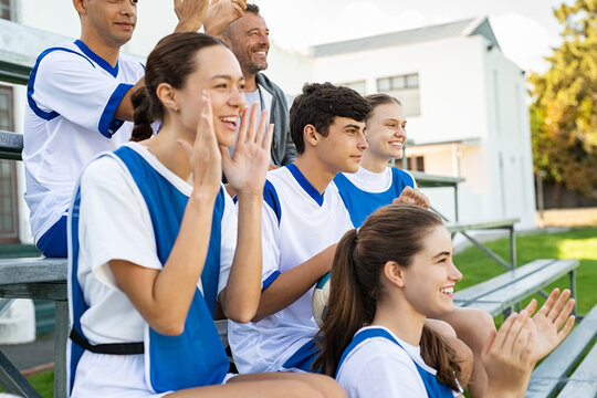 Soccer team mates cheering on the bench