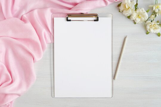 Feminine work desk with empty clipboard mockup, wedding planner, list, pink scarf and flowers, flat lay, top view.