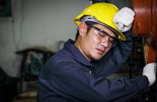 Asian male worker Dressed in a uniform, helmet and safety glasses, take a nap.