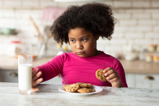 Grumpy Little Black Girl Refusing Milk And Eating Cookies In Kitchen