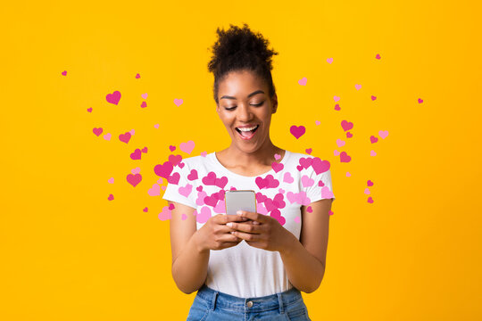 Black woman sending love message on cellphone, hearts flying away