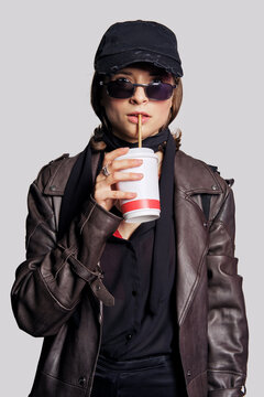 Girl in leather coat, black blouse, silk scarf and basebal cap with takeaway cup
