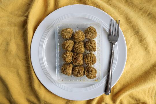 Falafel als Fastfood in einer Folienverpackung mit Teller und Besteck