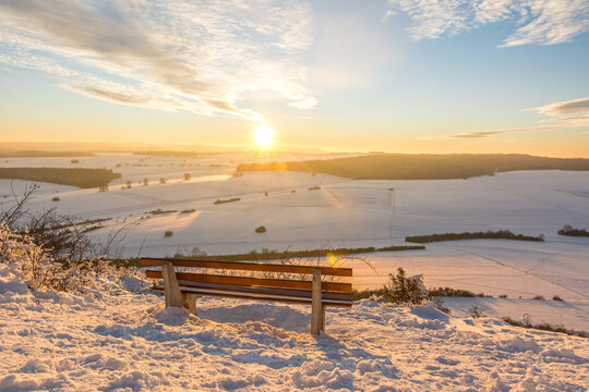Scenic colourful sunset over beautiful winter landscape in the Swabian Alps with bench in the foreground