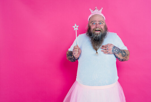 Funny man dancing and having fun wearing  a ballet outfit. Happy princess on a pink colored background