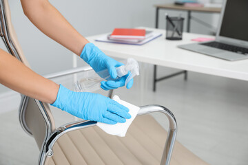Woman cleaning armchair with antiseptic in office, closeup