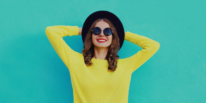 Portrait of beautiful young woman wearing a black round hat, yellow sweater on a blue background