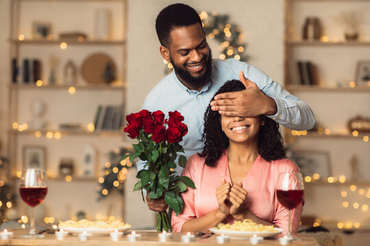Young black man giving flowers to woman, covering eyes