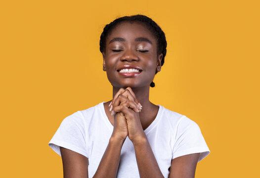 African American Woman Praying Standing On Yellow Studio Background