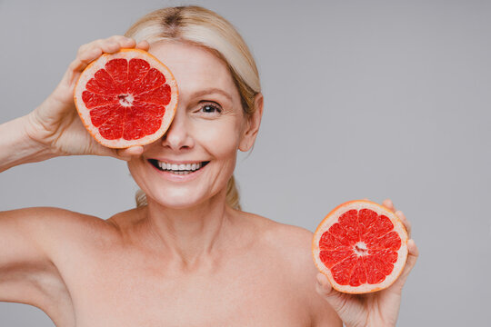 Cheerful pure skin caucasian woman holding grapefruit close to her face isolated over grey background