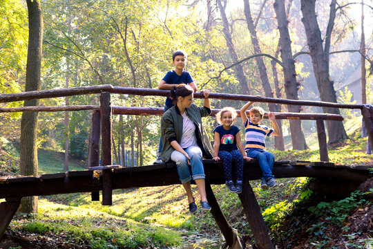 Mother with three kids relaxing on wooden bridge in the forest.