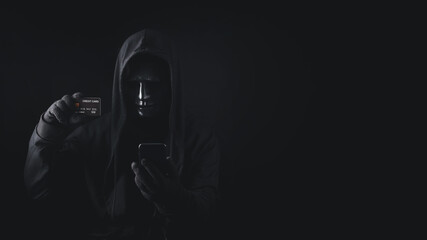 Dangerous anonymous hacker man in hooded use smartphone holding credit card, break security data and hack password with personal Bank account. Internet crime cyber attack security concept - fototapety na wymiar