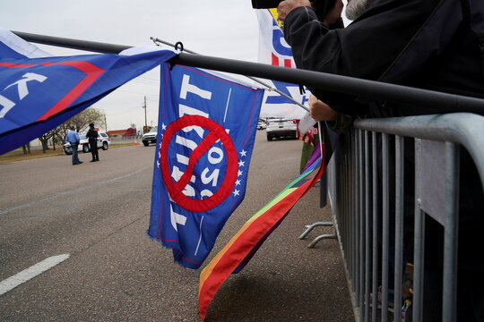 Protesters of the visit of U.S. President Donald Trump wave their flags among his supporters as they wait for his convoy to pass in McAllen, Texas