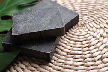 Wall Mural - Natural tar soap on wicker mat with green leaf, closeup