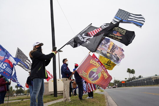 Supporters of U.S. President Donald Trump wave their flags near the airport