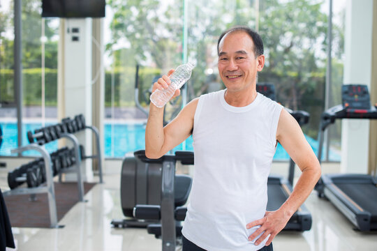 Elderly asian man in a gym drinking water after exercise and background blur diverse equipment and machines at the gym room. Fitness, sport, Advertise concept