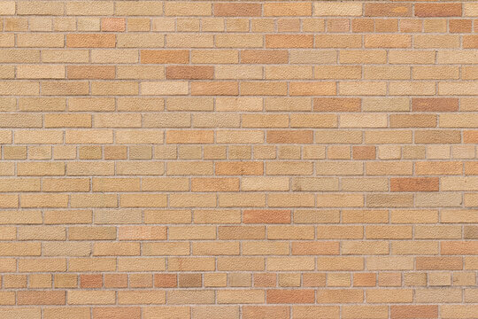 Full frame texture background of a vintage weathered brick wall in common bond pattern, with bricks in varying shades of orange and beige.