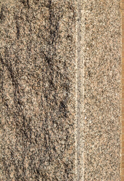 Full frame texture background of a vintage granite stone wall with flecks of beige black and brown colors and rough texture, in natural sunlight