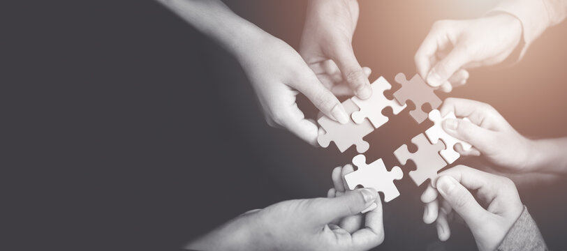 CSR (coporate social responsibility) or teamwork concept.Hands holding jigsaw.Close up top view of young business people putting jigsaw for team together.Charity, volunteer. Unity, team business.