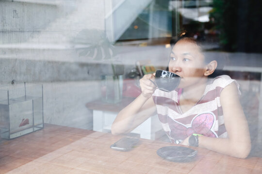 Thoughtful Woman Drinking Coffee While Looking Away Seen Through Window In Cafe
