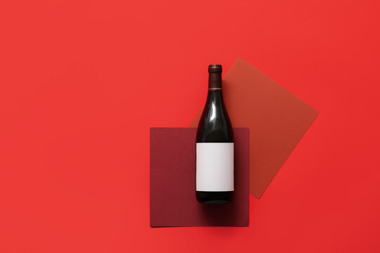 Bottle of wine with blank label on color background
