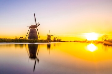Obraz Traditional Windmills By Lake Against Sky During Sunset - fototapety do salonu
