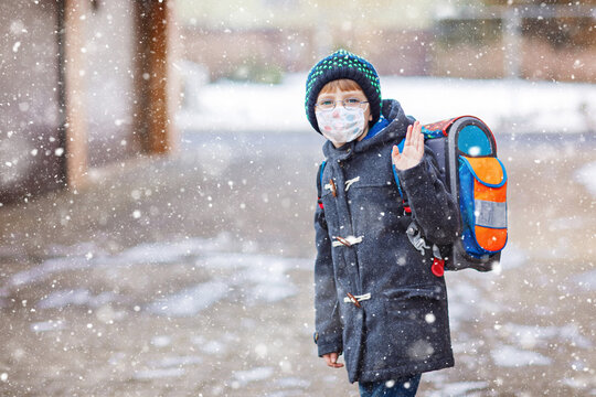 Little kid boy with glasses wearing medical mask on the way to school after lockdown. Child backpack satchel. Schoolkid on winter day with warm clothes. Quarantine time during corona pandemic disease