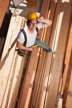 Mixed race construction worker standing on lumber