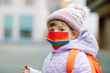 Little kid girl wearing medical mask on the way to kindergarten, playschool or nursery. Child with backpack satchel on cold day with warm clothes. Lockdown and quarantine time during corona pandemic