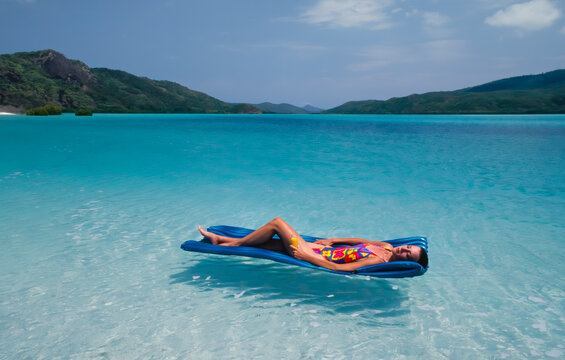 Young Woman floating on a Lilo at Whitehaven Beach - Queensland