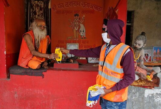 A man distributes face masks amongst Sadhus or Hindu holy men as part of a preventive measure against the coronavirus disease (COVID-19) at Sagar Island