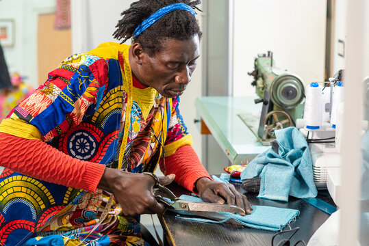 african tailor from senegal at work in his workshop, handcrafted production of european fashion clothes with african wax fabrics, concept of diversity and integration, new small socialbusiness