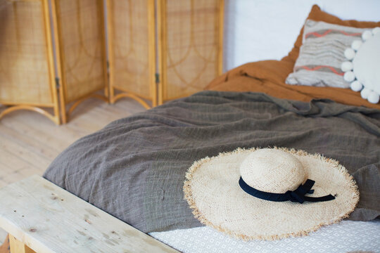 Straw hat on the bed bohemian bedroom