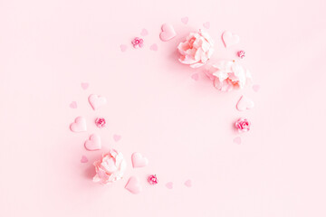 Valentine's Day background. Wreath made of pink flowers, hearts on pastel pink background....
