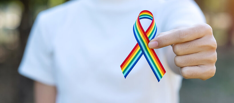 hand showing LGBTQ Rainbow ribbon against sky background in the morning. Support Lesbian, Gay, Bisexual, Transgender, Queer community and Rights concept