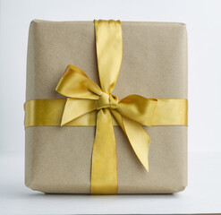 Gift box with golden bow to a celebration on white background