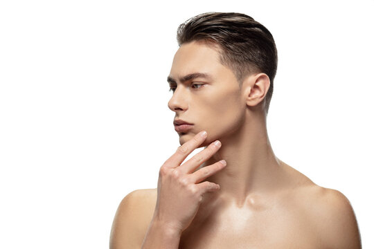 Thoughtful. Portrait of young man isolated on white studio background. Caucasian attractive male model. Concept of fashion and beauty, self-care, body and skin care. Handsome boy with well-kept skin.