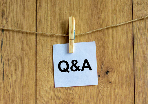 Questions and answers symbol. White paper. Words 'Q and A, Questions and answers'. Beautiful wooden background. Business and Q and A, questions and answers concept, copy space.