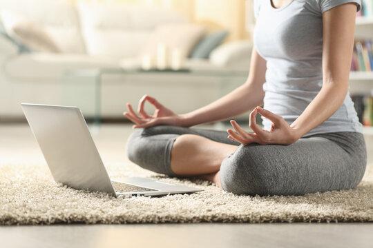 Woman watching video tutorial on laptop doing yoga