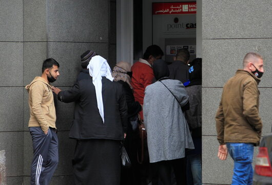 People gather at an ATM of a bank ahead of a tightened lockdown and a 24-hour curfew to curb the spread the coronavirus disease (COVID-19) outbreak in Sidon