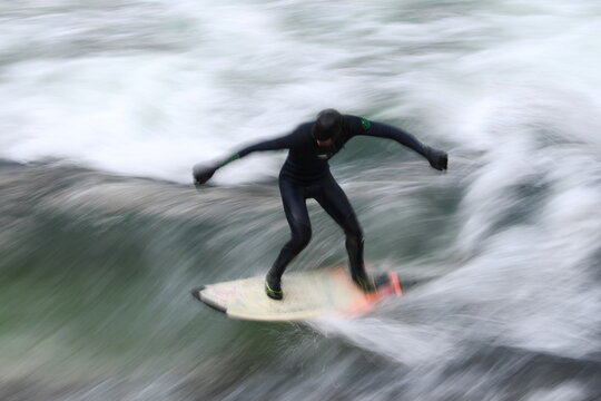 Surfer rides a wave in the Eisbach river in the English Garden in Munich